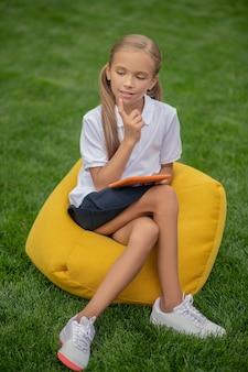 W myślach. śliczna jasnowłosa uczennica siedzi na krześle z torbą i wygląda zamyślona