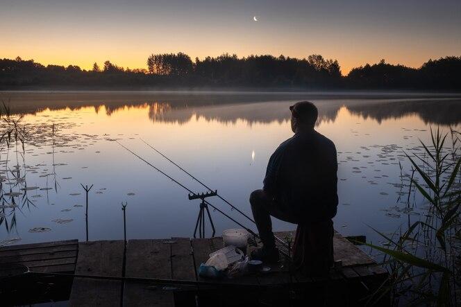 W nocy na pomoście siedzi rybak z wędkami do łowienia na jeziorze