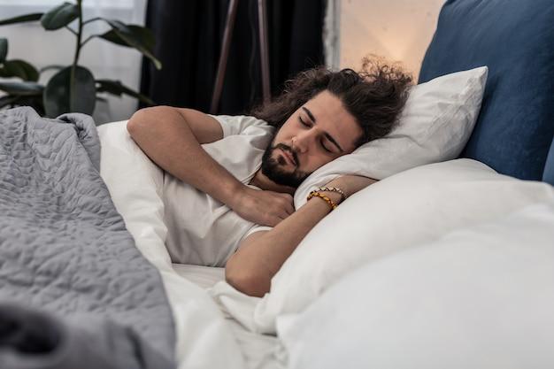 W nocy. przyjemny brunet leżący w łóżku podczas odpoczynku w domu
