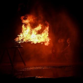 W nocy strażacy gaszą płonący ogień.