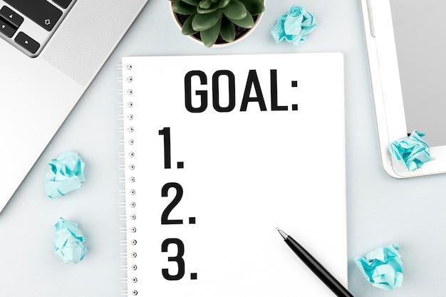 W notatce napisz goal. laptop, kawałki papieru, długopis i roślina na biurku. płaski świeckich, widok z góry. koncepcja planowania.