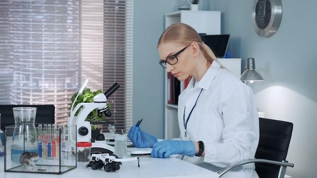 W nowoczesnym laboratorium badawczym naukowiec eksperymentuje z lupą i szczypcami chirurgicznymi