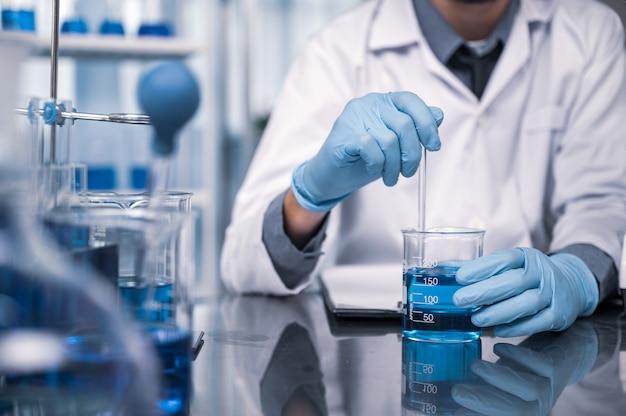 W nowoczesnym laboratorium badawczym naukowiec przeprowadza eksperymenty przez syntezę związków
