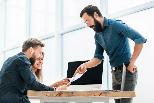 W nowym biurze młodzi specjaliści pracują nad dokumentacją biznesową. biurowe dni powszednie
