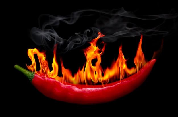 W ogniu czerwony chili pieprz na czarnym tle