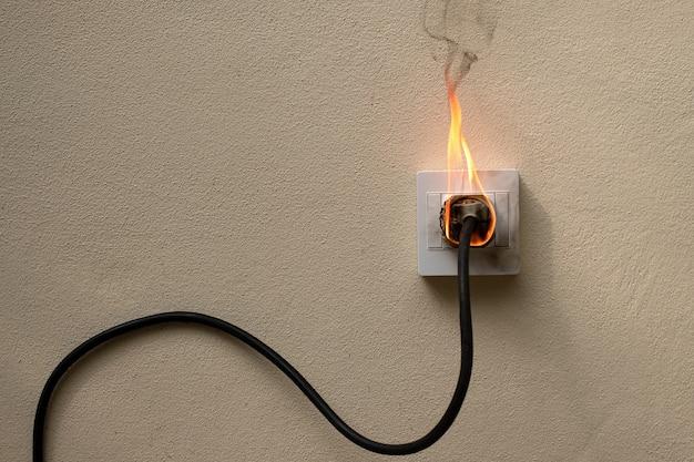 W ogniu wtyczka przewodu elektrycznego gniazdo na ścianie betonowej odsłoniętym tle betonu z miejsca na kopię