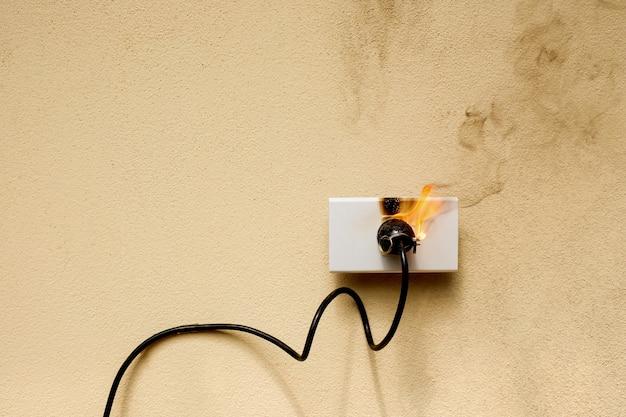 W ogniu wtyczka przewodu elektrycznego gniazdo na tle ściany betonowej