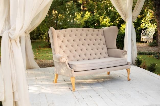 W ogrodzie znajduje się podium, na którym znajduje się sofa w stylu prowansalskim lub rustykalnym