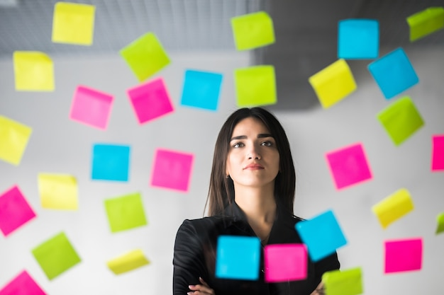 W oknie świeci słońce. klei naklejki i przemyśla projekt. biznes kobieta myśli nad planami na naklejkach.