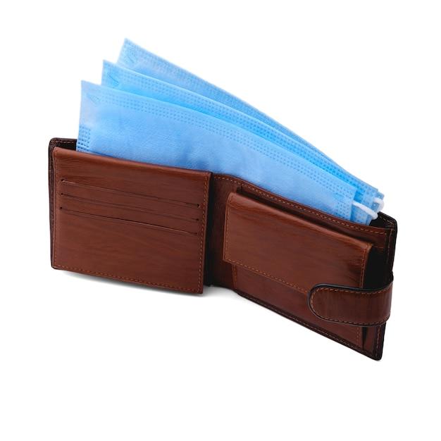 W otwartym brązowym skórzanym portfelu znajdują się trzy niebieskie jednorazowe maski medyczne