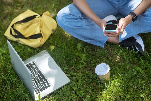 W parku. ładna dziewczyna w różowej koszulce siedząca na trawie w parku i studiująca