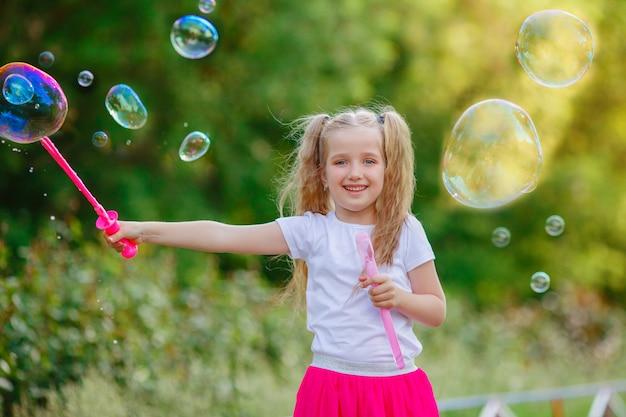 W parku latem dziewczyna dmucha bańki mydlane