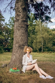 W parku. młoda kobieta siedzi pod drzewem w parku