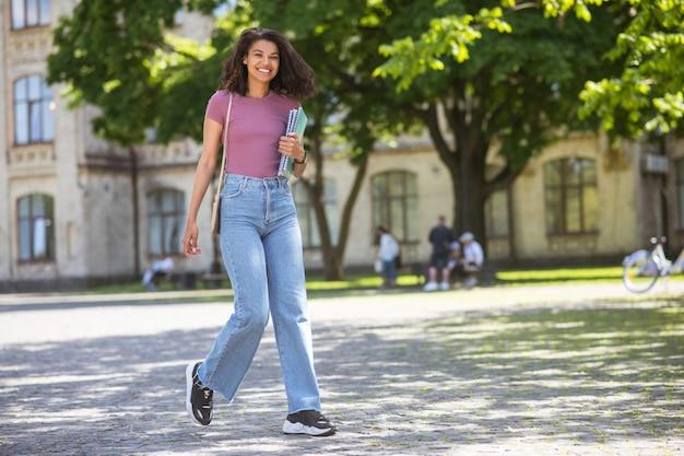W parku. śliczna dziewczyna w dżinsach spacerująca po parku