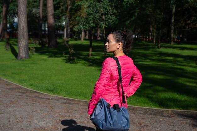 W parku stoi młoda kobieta z torbą sportową na ramieniu. widok z boku.