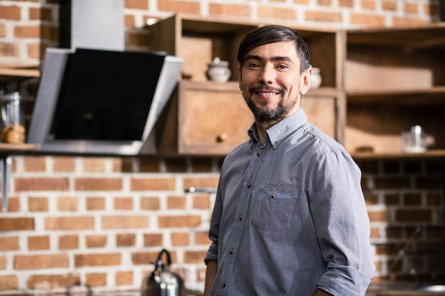 W pasie uśmiechnięty brodaty mężczyzna stojący w kuchni, jednocześnie dzieląc się pozytywnością