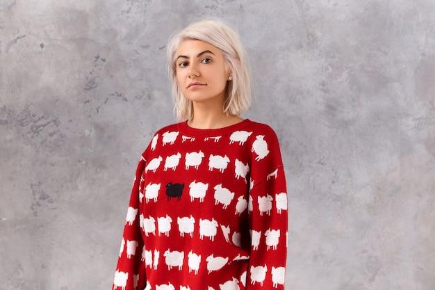 W pasie wizerunek modnej młodej kobiety z farbowaną niechlujną fryzurą bob pozującą w czerwonym swetrze z białymi owieczkami, odizolowaną przy pustej ścianie z miejscem na tekst reklamowy lub informacje