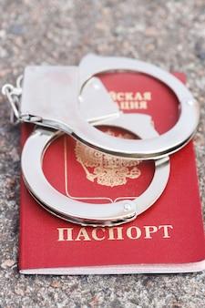 W paszporcie znajdują się srebrne kajdanki. napis w języku rosyjskim paszport. zdjęcie wysokiej jakości
