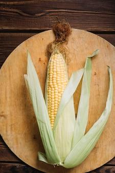 W pełni uprawiana kukurydza z liśćmi na desce do krojenia