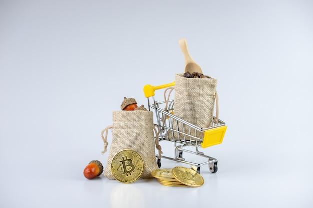 W pełni wypełnione worki z żołędziami i ziarnami kawy, na wózku, obok złotych monet.