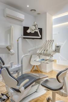 W pełni wyposażone nowoczesne pudełko kliniki dentystycznej, z białymi ścianami i drewnianą podłogą. radiografia stomatologiczna pokazana na monitorze.