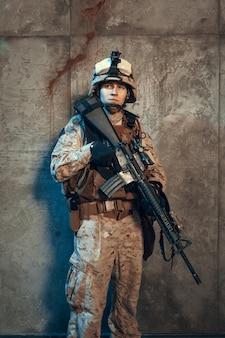 W pełni wyposażony żołnierz armii w kamuflażu i hełmie, uzbrojony w pistolet i karabin szturmowy