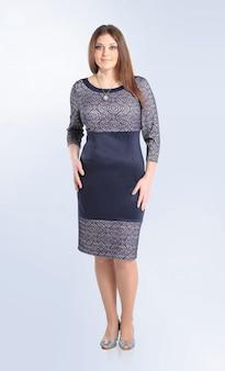 W pełni wzrostu młoda kobieta w stylowej sukience