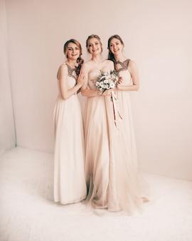 W pełnym wzroście. panna młoda i jej przyjaciele w sukniach na ceremonię ślubną. zdjęcie z miejscem na kopię
