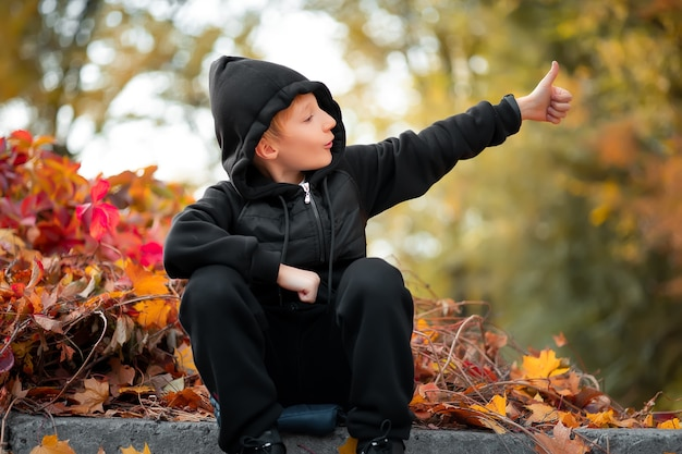 W pięknym jesiennym parku na granicy siedzi chłopiec, który pokazuje kciuk w górę.