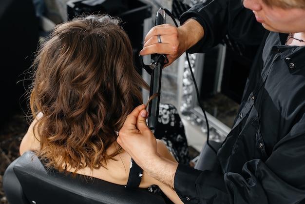 W pięknym, nowoczesnym salonie kosmetycznym profesjonalna stylistka strzyże i uczesuje młodą dziewczynę. piękno i moda.