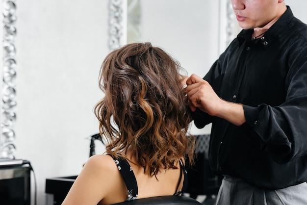 W pięknym, nowoczesnym salonie kosmetycznym profesjonalna stylistka wykonuje fryzurę i fryzurę dla młodej dziewczyny. piękno i moda.