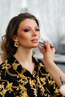 W pięknym, nowoczesnym salonie kosmetycznym profesjonalna wizażystka wykonuje makijaż dla młodej kobiety.