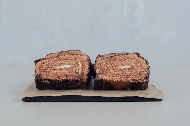 W plasterkach roll słodkiej czekolady na desce.