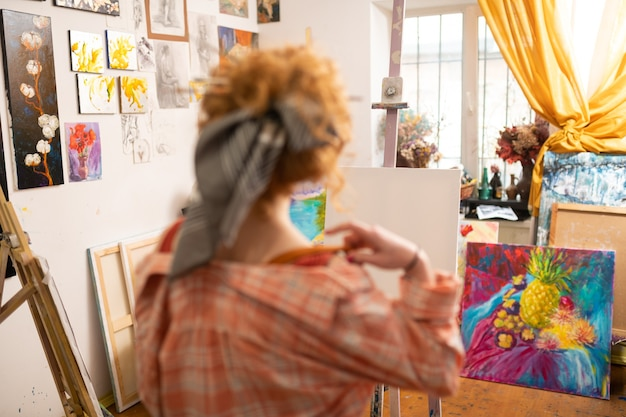 W pobliżu białego płótna. rudowłosy artysta stojący w pobliżu białego płótna i okna przed rozpoczęciem pracy
