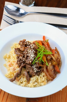 W pobliżu biały talerz ryżu, mięsa, warzyw z przyprawami oraz łyżka i widelec