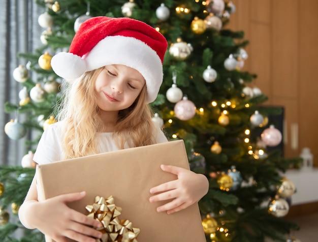 W pobliżu choinki bawi się dziewczyna z prezentami. wnętrze salonu z choinką i dekoracjami. nowy rok. rozdawanie prezentów.