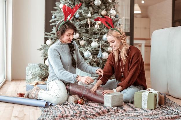 W pobliżu choinki. przyjemne, spokojne dziewczyny pomagające sobie nawzajem w pakowaniu prezentów świątecznych dla krewnych i przyjaciół
