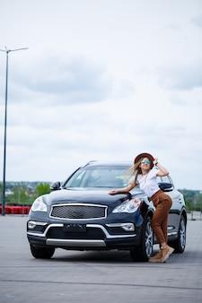 W pobliżu czarnego samochodu stoi piękna dziewczyna o europejskim wyglądzie w okularach i brązowym kapeluszu. zdjęcie w pobliżu samochodu.