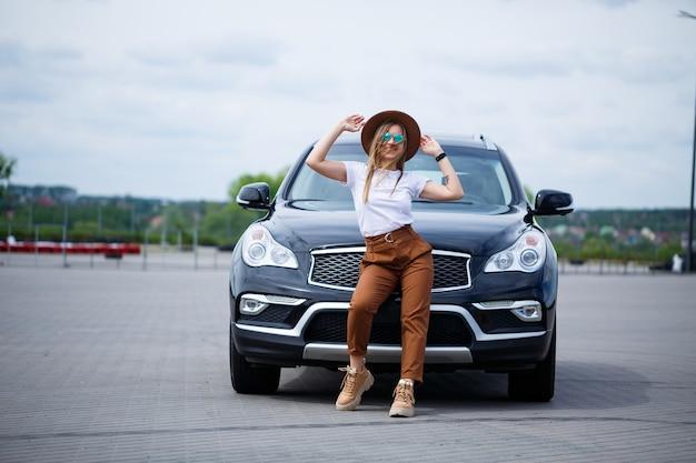 W pobliżu czarnego samochodu stoi piękna dziewczyna o europejskim wyglądzie w okularach i brązowym kapeluszu.
