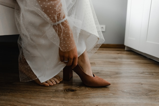 W pobliżu drzwi do szafy stoją damskie buty ślubne. buty panny młodej.