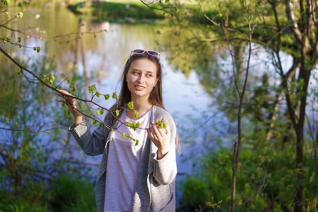W pobliżu jeziora idzie młoda piękna dziewczyna w okularach przeciwsłonecznych, trzymając w rękach gałąź drzewa