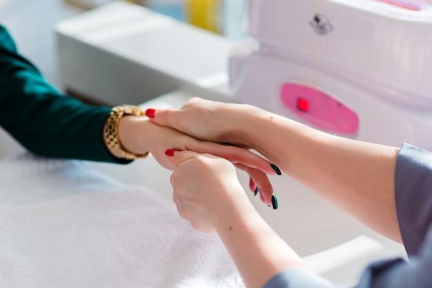 W pobliżu kobiecych dłoni masażysty wykonaj masaż punktowy dłoni