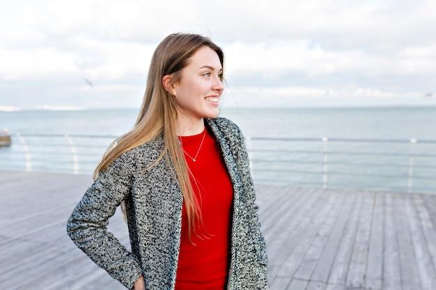 W pobliżu morza szczęśliwa uśmiechnięta długowłosa kobieta z dużymi niebieskimi oczami w czerwonej koszuli i szarym płaszczu