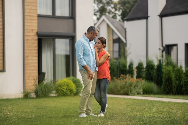 W pobliżu prywatny dom. mąż i żona stoją w pobliżu swojego prywatnego domu i oddychają świeżym powietrzem