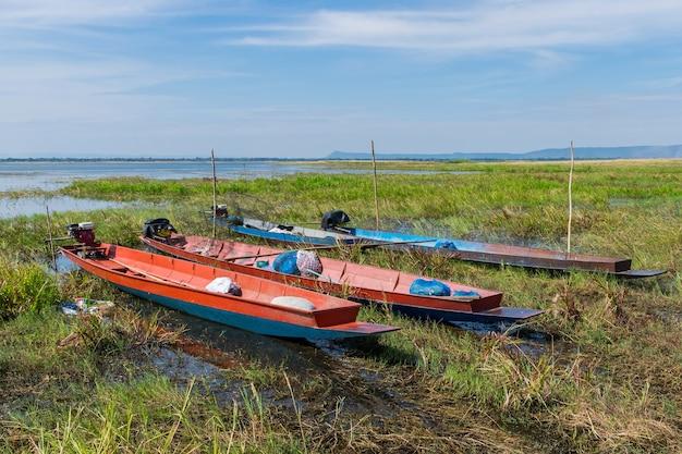 W pobliżu rzeki przycumowane są łodzie z długim ogonem