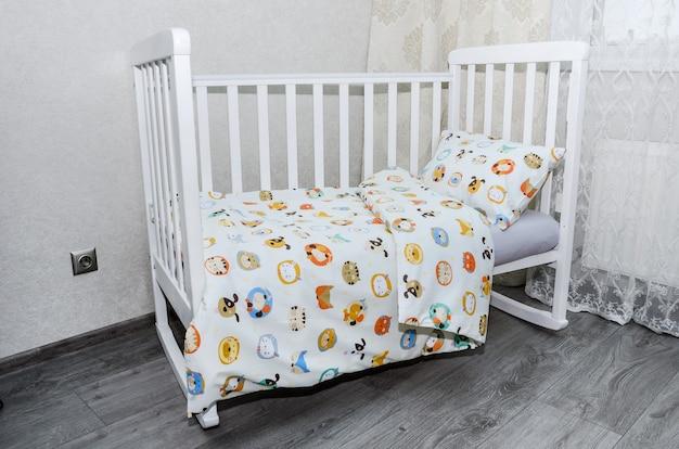 W pokoju łóżeczko z poduszką i podstawką na koc