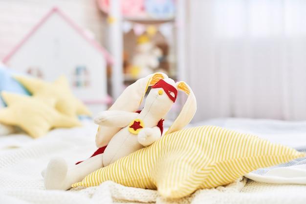 W pokoju siedzi pluszowy królik uszyty z tkaniny w kostiumie superbohatera