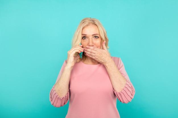 W połowie blond kobieta z telefonem zamykając usta na białym tle.