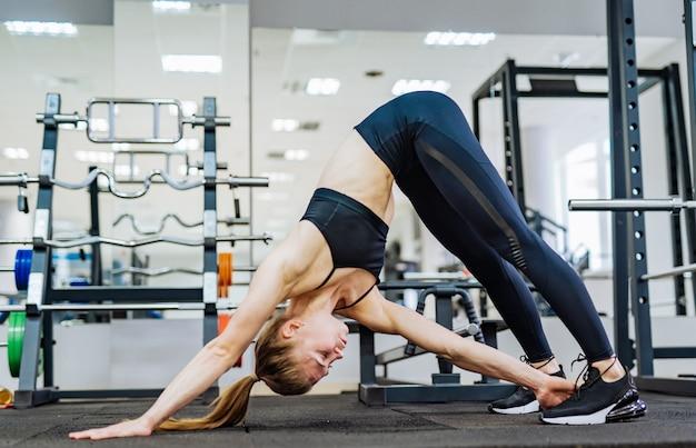 W połowie bocznego widoku strzał sprawności fizycznej dobrze kształtująca kobieta wykonuje w dół psią pozę z ręką dotyka jej nogę na podłoga gym.