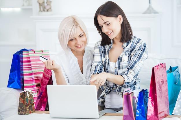 W połowie dorosła kobieta i jej córka robi zakupy online w domu. szczęśliwa rodzina kupuje w domu towary internetowe. kobiety zamawiające online.